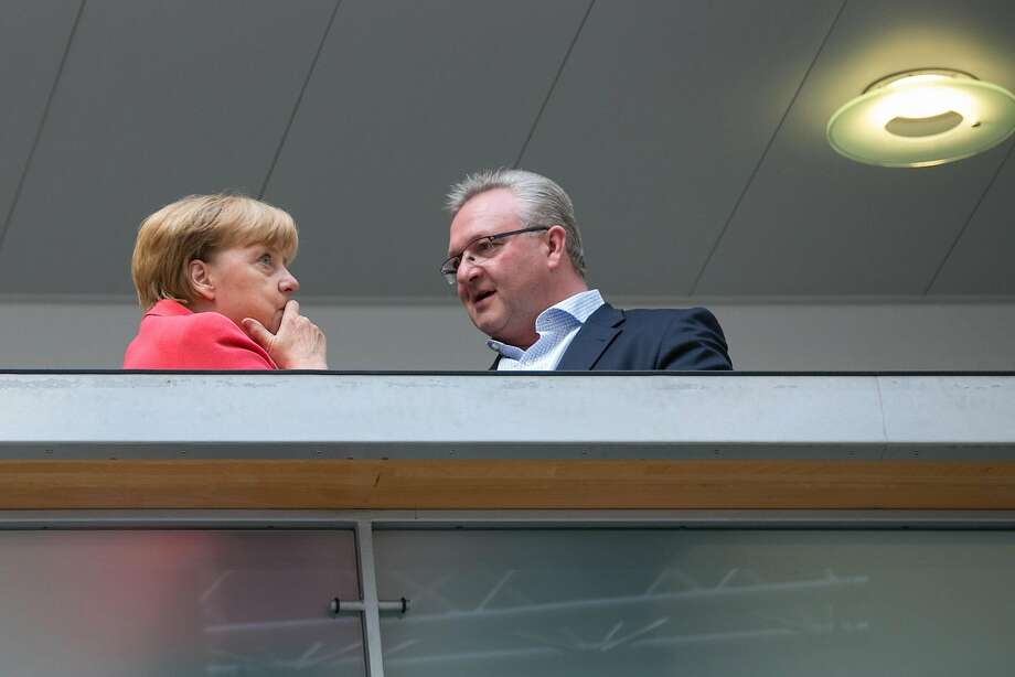 Chancellor Angela Merkel confers with Frank Henkel, her party's mayoral candidate in Berlin. Photo: Krisztian Bocsi, Bloomberg