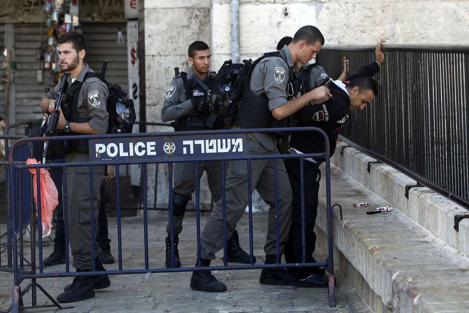 Israeli border officers search a Palestinian man near the scene of a stabbing attack in Jerusalem's Old City. Two officers were injured, and the attacker was shot and wounded. Photo: Mahmoud Illean, Associated Press