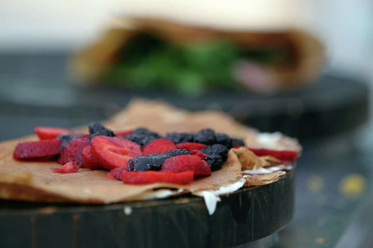 Berries are added to a crepe being made at Melange Creperie