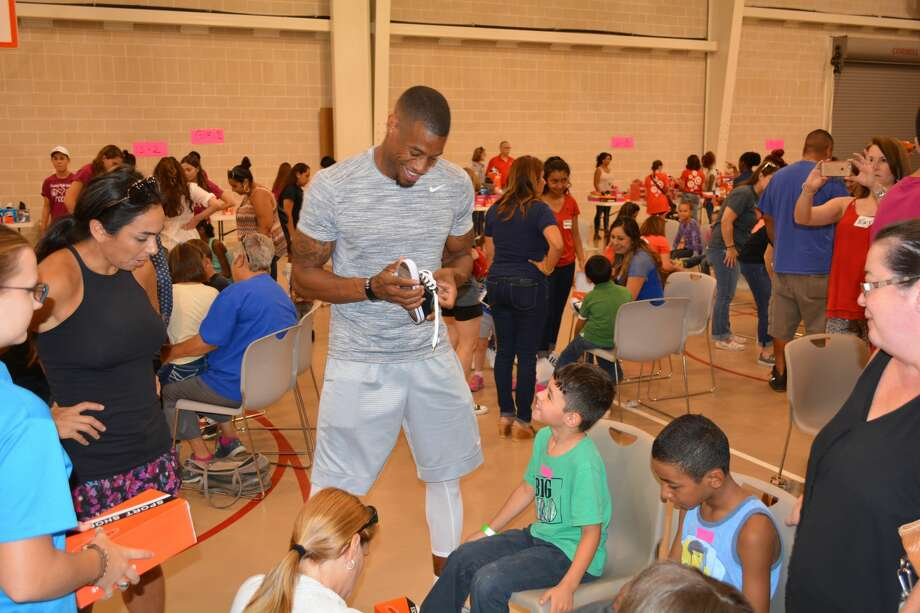 Celebrities like former Spur Antonio Daniels and news personalities, as well as volunteers from local businesses volunteered at The Salvation Army's 35th Annual Shoe-In on Sept. 17, 2016 where more than 2,000 children received free shoes. Photo: Brad Mayhar