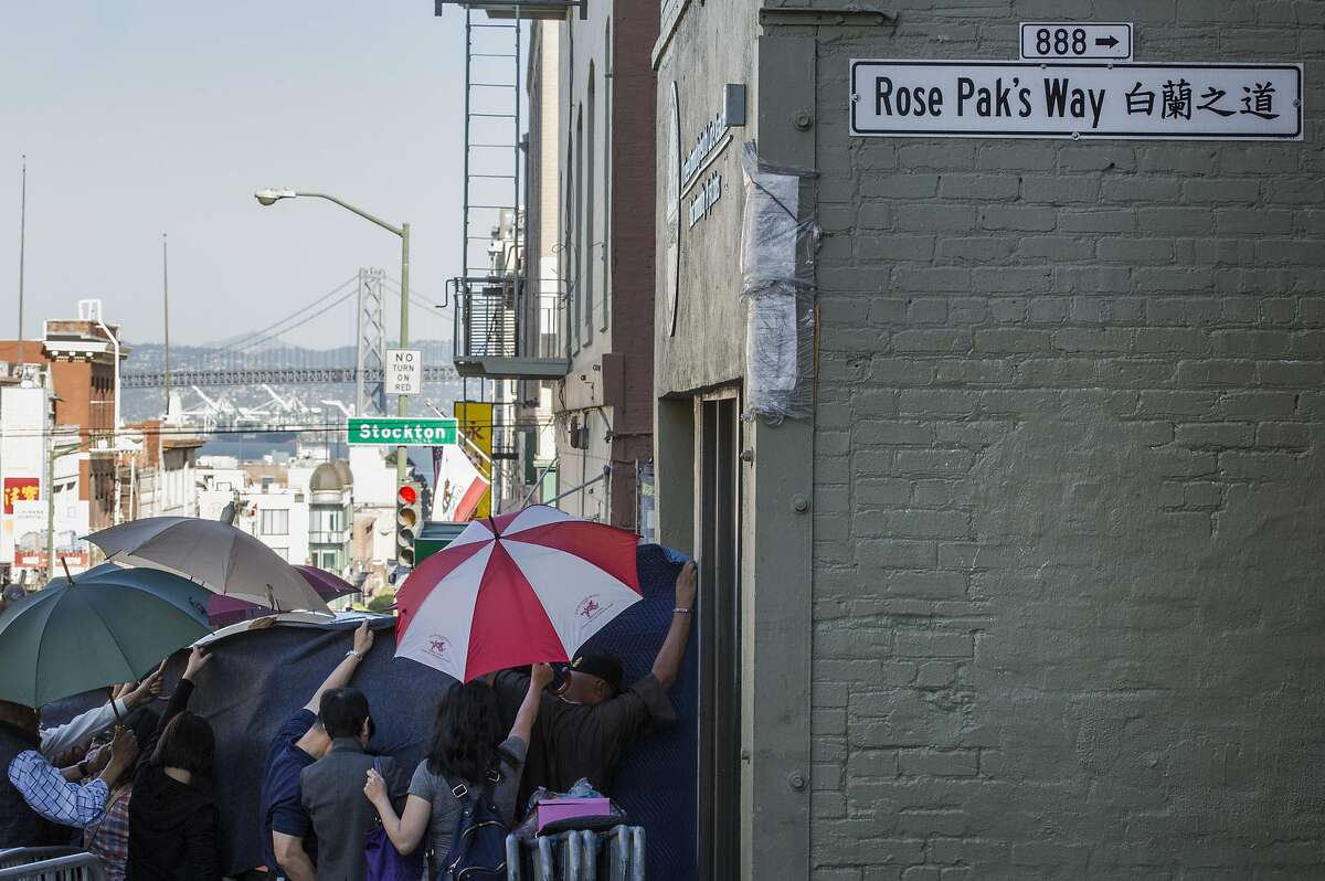 The body of Rose Pak is being placed into a car, as people conceal the view of the vehicle with blankets and umbrellas, Sunday, Sept. 18, 2016 in San Francisco, Calif.