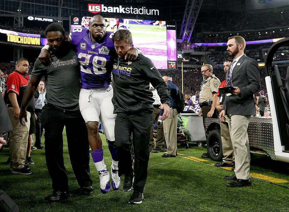 Minnesota Vikings running back Adrian Peterson is helped to the locker room in the third quarter of Sunday night's game after suffering a knee injury against the Green Bay Packers. Photo: Carlos Gonzalez, TNS