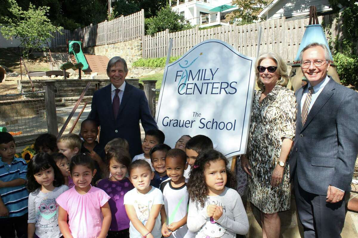 Peter Grauer, left, and Laurie Grauer attend the dedication of The Grauer Preschool in Greenwich on Friday with Family Centers President Bob Arnold, right, and some children from the school.
