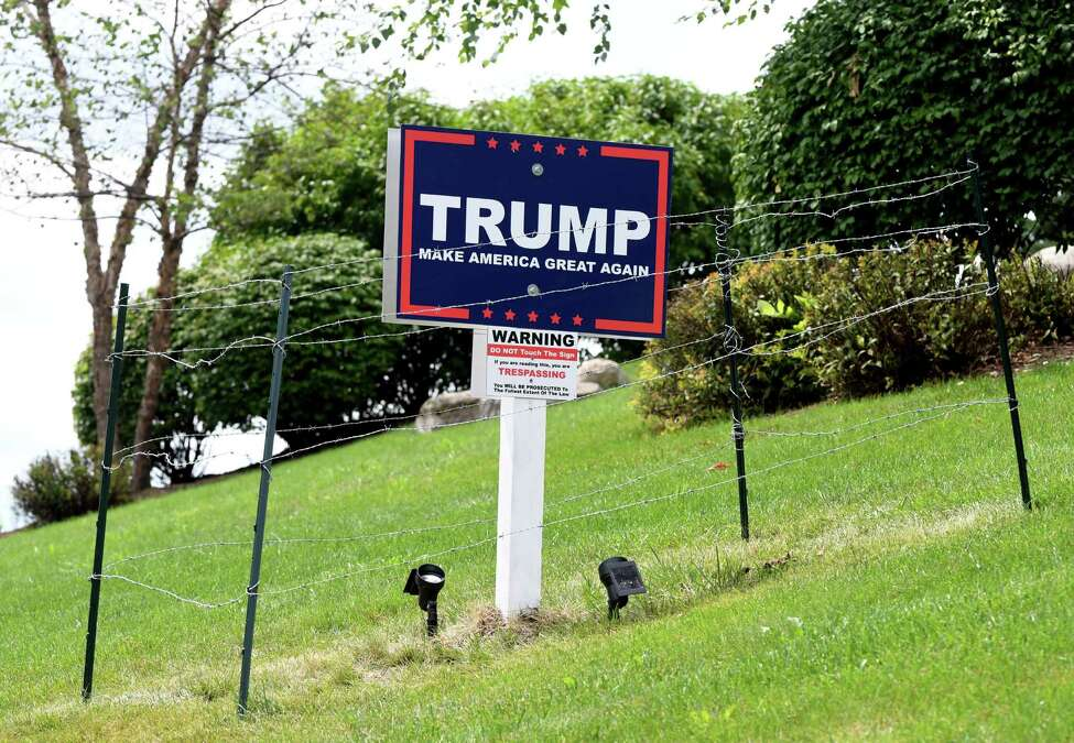 A barbed wire fence and other security measures surround a political lawn sign for Republican presidential candidate Donald J. Trump on Monday, Aug. 15, 2016, on East Hills Blvd in Colonie, N.Y. The property belongs to builder Robert Marini. (Will Waldron/Times Union archive)