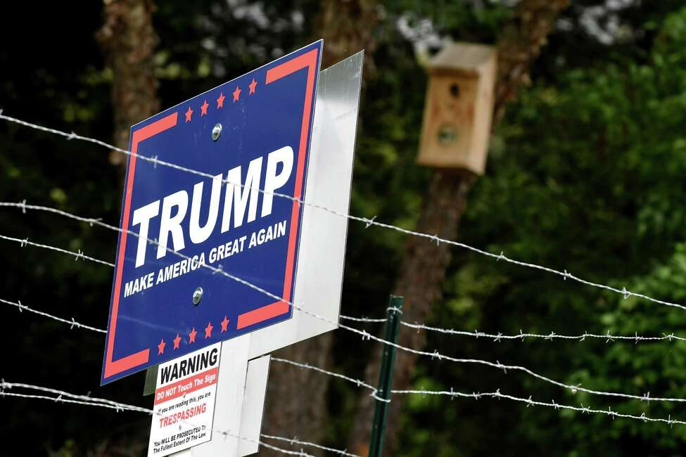 A barbed wire fence and other security measures surround a political lawn sign for Republican presidential candidate Donald J. Trump on Monday, Aug. 15, 2016, on East Hills Blvd in Colonie, N.Y. The property belongs to builder Robert Marini. (Will Waldron/Times Union)