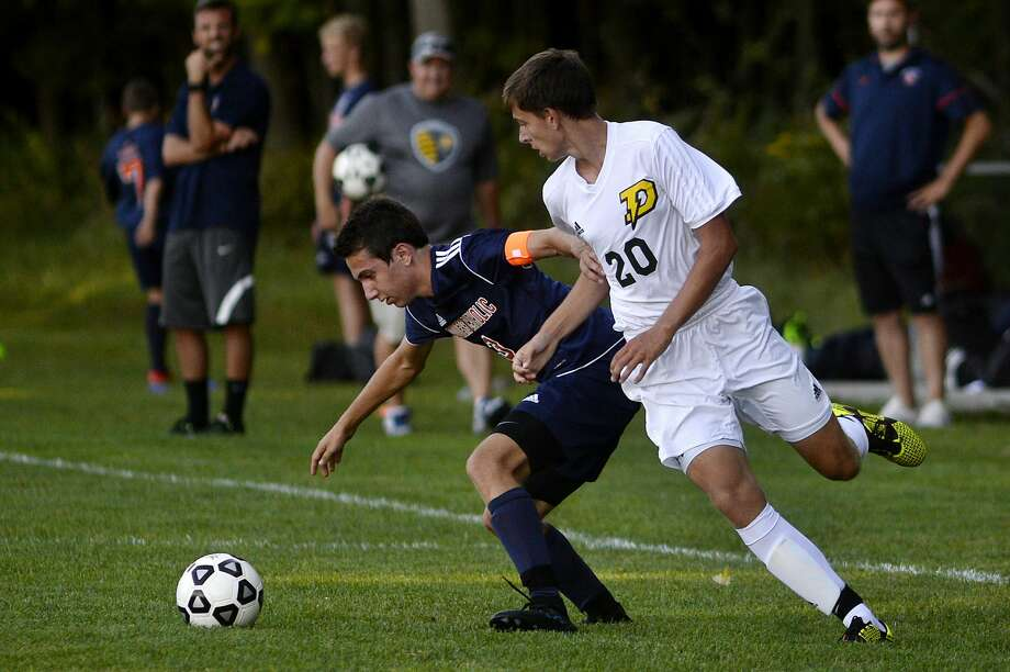 Dow's Zachary Lyman, right, moves in on Flint Powers' Steven Tuttle during the first half on Monday at Dow High School. Dow won 3-1. Photo: Nick King/Midland Daily News
