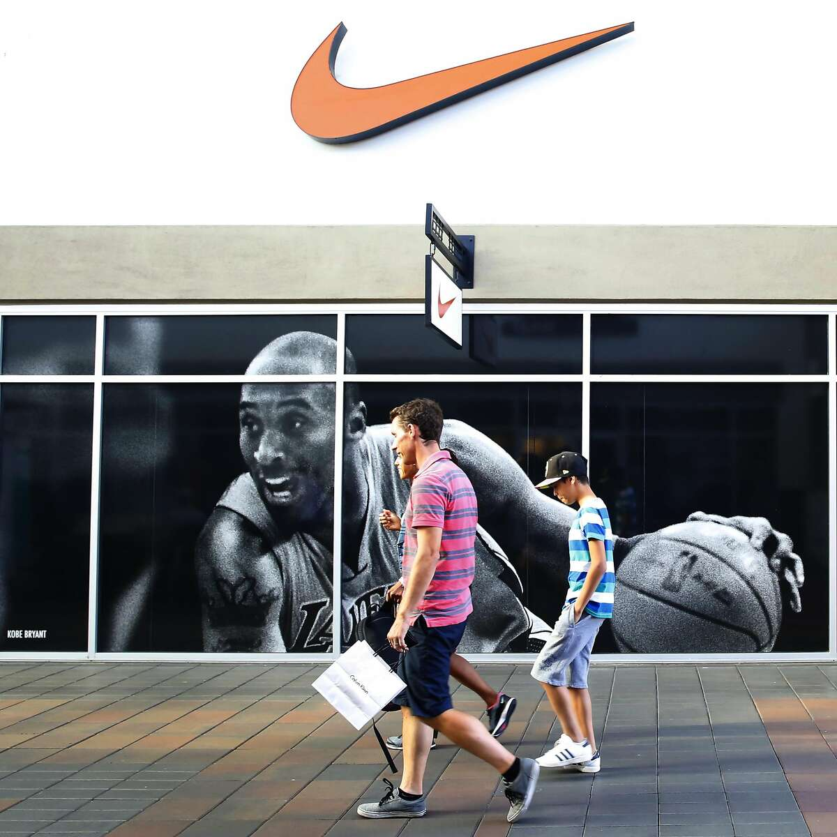 View of shoppers passing the Nike store at San Francisco Premium Outlets on Wednesday, September 14, 2016, in Livermore, Calif.