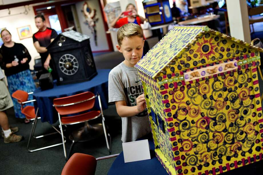 Kellan Galloway, 10, checks out a little library decorated by artist Linda Z. Smith during a thank-you party on Monday at Creative 360 for artists who've decorated 15 Little Free Libraries that Jeff Havens plans to deliver in Midland to over 35 people who have requested a library for their yards. Kellan's family will be one of the private residents displaying a library. Chippewa Nature Center, the Community Center, the Salvation Army, West Midland Family Center, and several others will be receiving them. Photo: Nick King/Midland Daily News