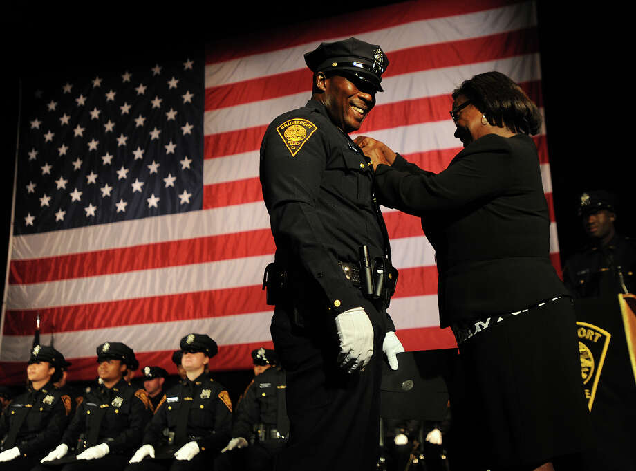 Bridgeport probationary police officer Kamar Gidden is pinned with his badge by his mother Melda Clarke at the Police Academy's swearing in ceremony at the Klein Memorial Auditorium in Bridgeport on Monday. Photo: Brian A. Pounds / Hearst Connecticut Media / Connecticut Post