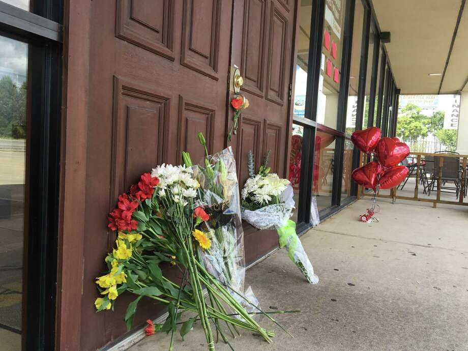 Flowers line the entrance of the Sunny Side of the Street on FM 2920 in Spring after the café's beloved chef was slain Sunday evening. / Keri Blakinger