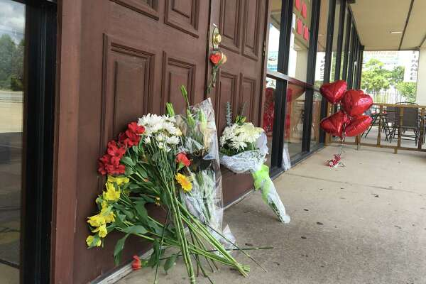Flowers line the entrance of the Sunny Side of the Street on FM 2920 in Spring after the café's beloved chef was slain Sunday evening.