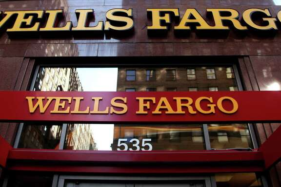 FILE - In this May 6, 2012, file photo, a Wells Fargo sign is displayed at a branch in New York. Wells Fargo is in the spotlight after its employees allegedly created 2 million bank and credit card accounts, transferred customers' money without telling them and even created fake email addresses to sign people up for online banking in an effort to meet lofty sales goals. When Wells Fargo CEO John Stumpf testifies before a Senate committee hearing Tuesday, Sept. 20, 2016, it won't be just his bank under fire for turning friendly branches into high-pressure sales centers. It'll be the entire industry. (AP Photo/CX Matiash, File)