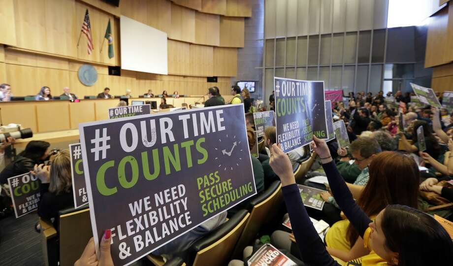 Supporters of new work scheduling rules hold up signs during a public comment period at a Seattle City Council meeting, Monday, Sept. 19, 2016, in Seattle. The Council was to vote Monday on new scheduling rules for hourly retail and food-service employees, including requiring employers to schedule shifts 14 days in advance and pay workers extra for certain last-minute scheduling changes. (AP Photo/Elaine Thompson) Photo: Elaine Thompson/AP