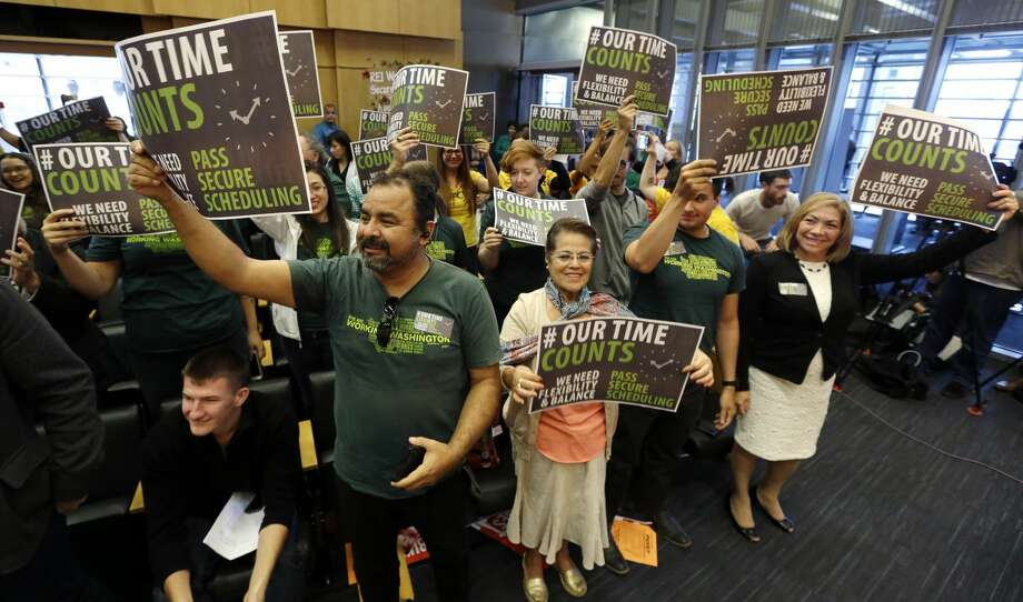 Supporters cheer as the Seattle City Council unanimously approved a new law designed to give hourly retail and food-service workers more predictability in their scheduling, Monday, Sept. 19, 2016, in Seattle. The new law is designed to give hourly retail and food-service workers more predictability in their scheduling. The measure approved Monday afternoon requires that large employers schedule shifts 14 days in advance, pay workers extra for certain last-minute scheduling changes and offer hours to existing employees before hiring new staff, among other provisions. (AP Photo/Elaine Thompson) Photo: Elaine Thompson/AP