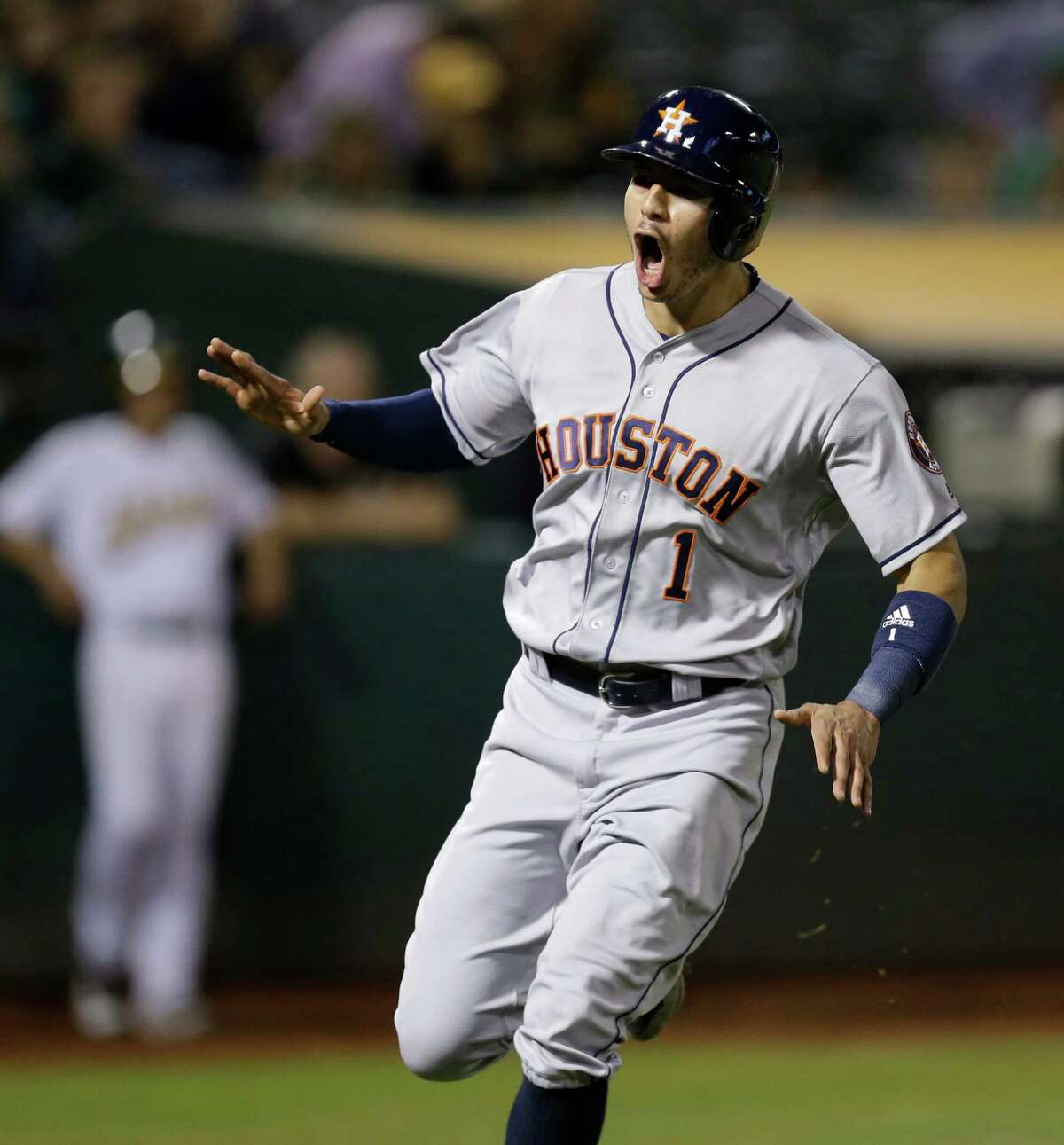 Houston Astros' Carlos Correa celebrates after scoring against the Oakland Athletics' in the ninth inning of a baseball game Monday, Sept. 19, 2016, in Oakland, Calif. (AP Photo/Ben Margot)