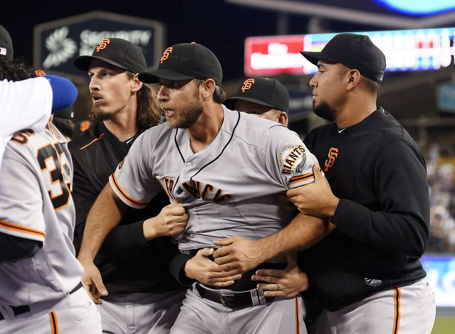 San Francisco Giants starting pitcher Madison Bumgarner, center, is pulled away by teammates after he and Los Angeles Dodgers' Yasiel Puig got into a scuffle that emptied both benches after Puig was thrown out at first by Bumgarner during the seventh inning of a baseball game, Monday, Sept. 19, 2016, in Los Angeles. (AP Photo/Mark J. Terrill) Photo: Mark J. Terrill, Associated Press