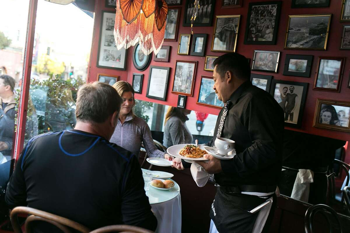 A server brings entrees to customers at The Stinking Rose in S.F.