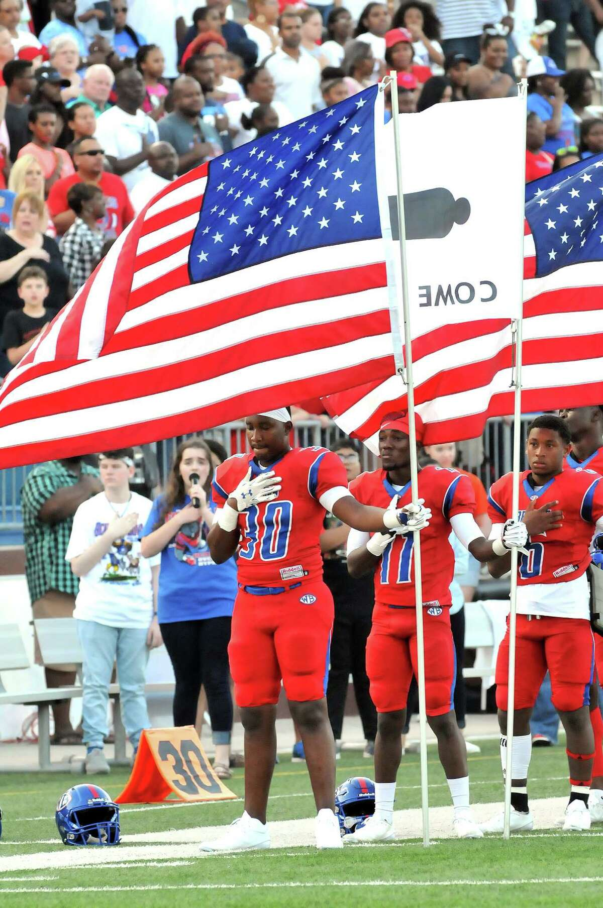 Members of the West Brook Bruins stand on Sept. 2 with their hands over their hearts, as several hold the American Flag as the national anthem is played prior to their Week 2 game against the Ozen Panthers at the Thomas Center in Beaumont. (Mike Tobias/The Enterprise)