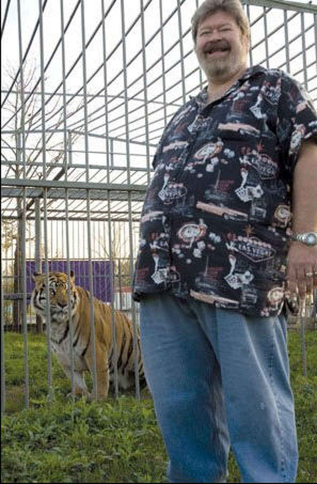 Man and beast Mike Sandlin, the owner of Tiger Truck Stop in Grosse Tete, La., and Tony, the live Bengal tiger living in an enclosure at the business just off Interstate 10. The tiger has become a point of contention with animal rights activists.