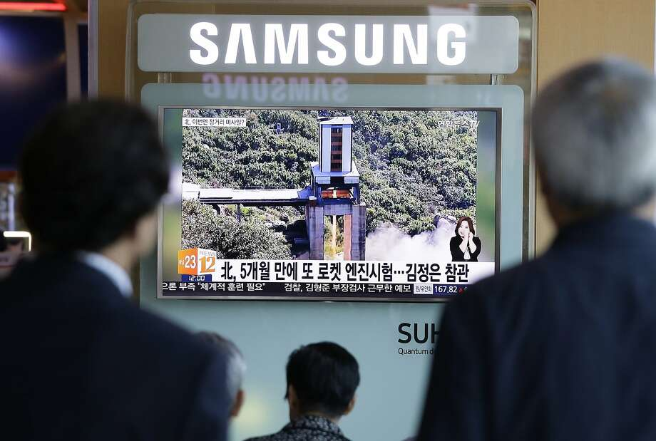 Seoul residents gather around a TV to watch the test of a high-powered engine of a carrier rocket. Photo: Ahn Young-joon, Associated Press