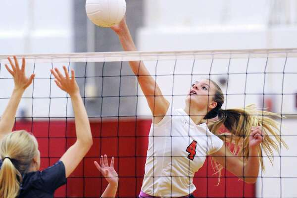 Tara Ford (#4) of Greenwich spikes the volleyball against Darien Friday in Greenwich. The Cards prevailed, 3-2.