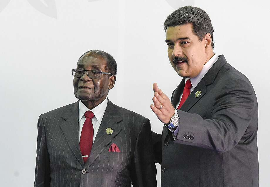 President Robert Mugabe (left) greets Venezuelan President Nicolas Maduro before the opening ceremony in the Non-Aligned Movement summit in Porlamar, Margarita Island, Venezuela, on September 17, 2016. With the left increasingly isolated by a crushing political and economic crisis, Venezuela is seeking the support of old friends at the Non-Aligned Movement summit it is hosting this weekend. / AFP PHOTO / JUAN BARRETOJUAN BARRETO/AFP/Getty Images Photo: JUAN BARRETO, AFP/Getty Images