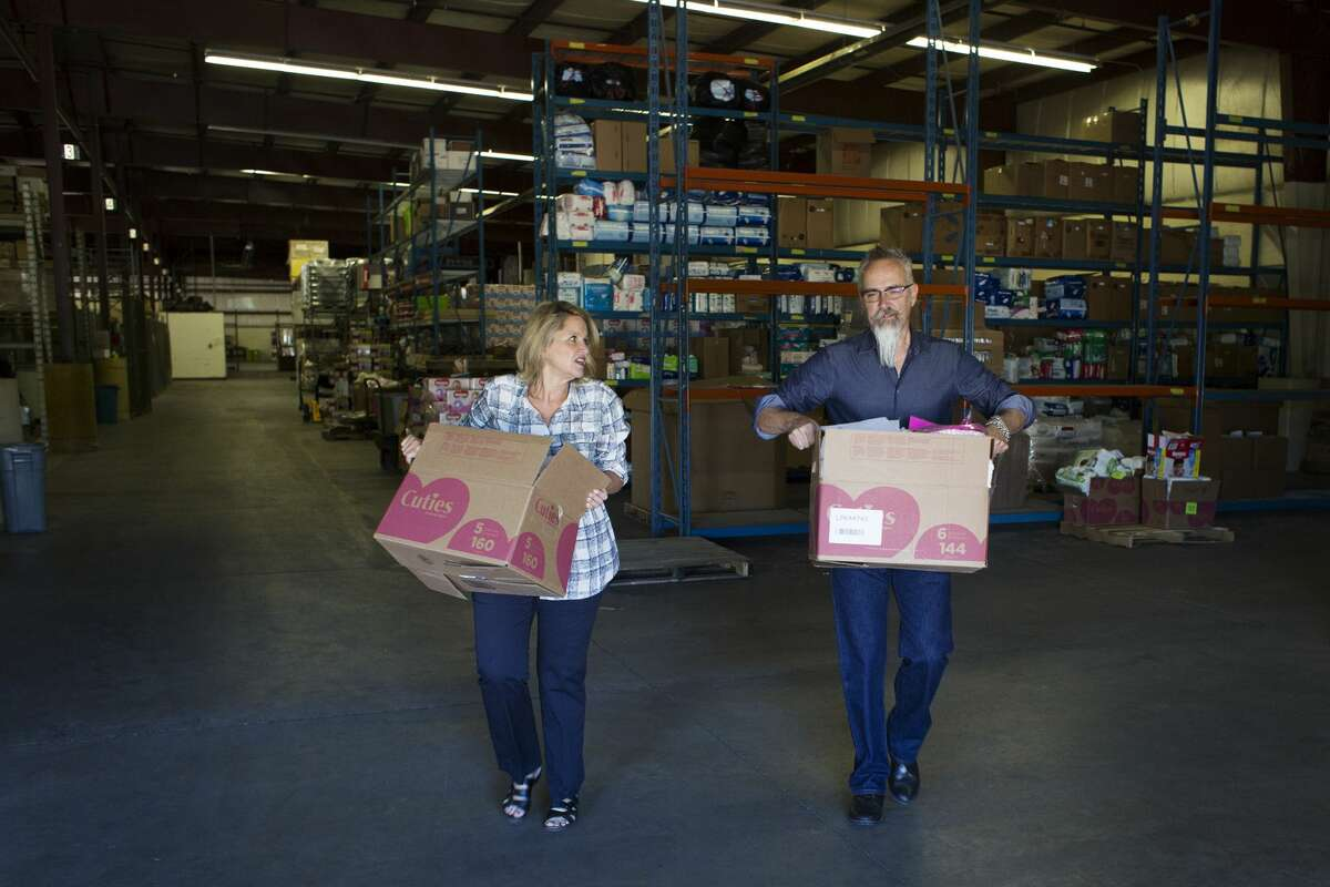 Debi Keyes, Founder and Executive Director of The Diaper Alliance, left, and Troy Moore, Director of Communication and Development, right, move boxes of diapers to the loading dock while helping to load diapers into the vehicles of partner agencies at The Diaper Alliance in Midland on Tuesday.