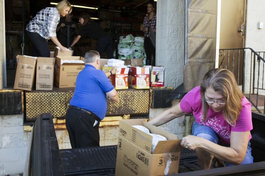 Pam Krueger, of Pregnancy Care Center in Saginaw, moves boxes of diapers in to the bed of her truck with the assistance of Debi Keyes, Founder and Executive Director of The Diaper Alliance, left, and Marty Wazbinski, President of Board Members of The Diaper Alliance,, center, while at the loading docks of The Diaper Alliance in Midland on Tuesday. Photo: Theophil Syslo