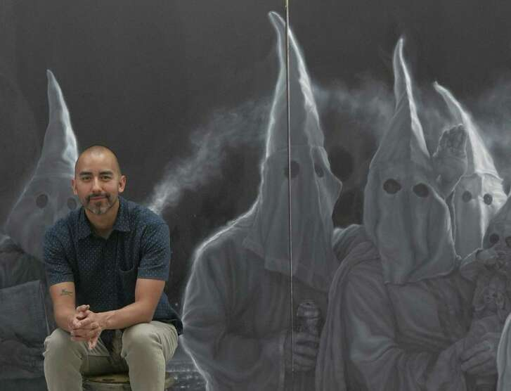 Vincent Valdez sits in his studio by his painting which depicts a Klu Klux Klan gathering.