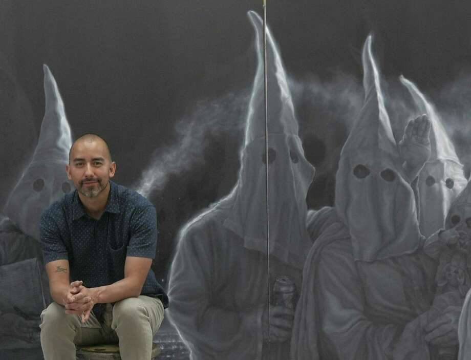 Former San Antonio artist Vincent Valdez sits in his studio by his painting that depicts a Klu Klux Klan gathering in September 2016. The work was shown at the David Shelton Gallery in Houston. Valdez said he wanted the work to make viewers uncomfortable. Photo: Billy Calzada /San Antonio Express-News / San Antonio Express-News