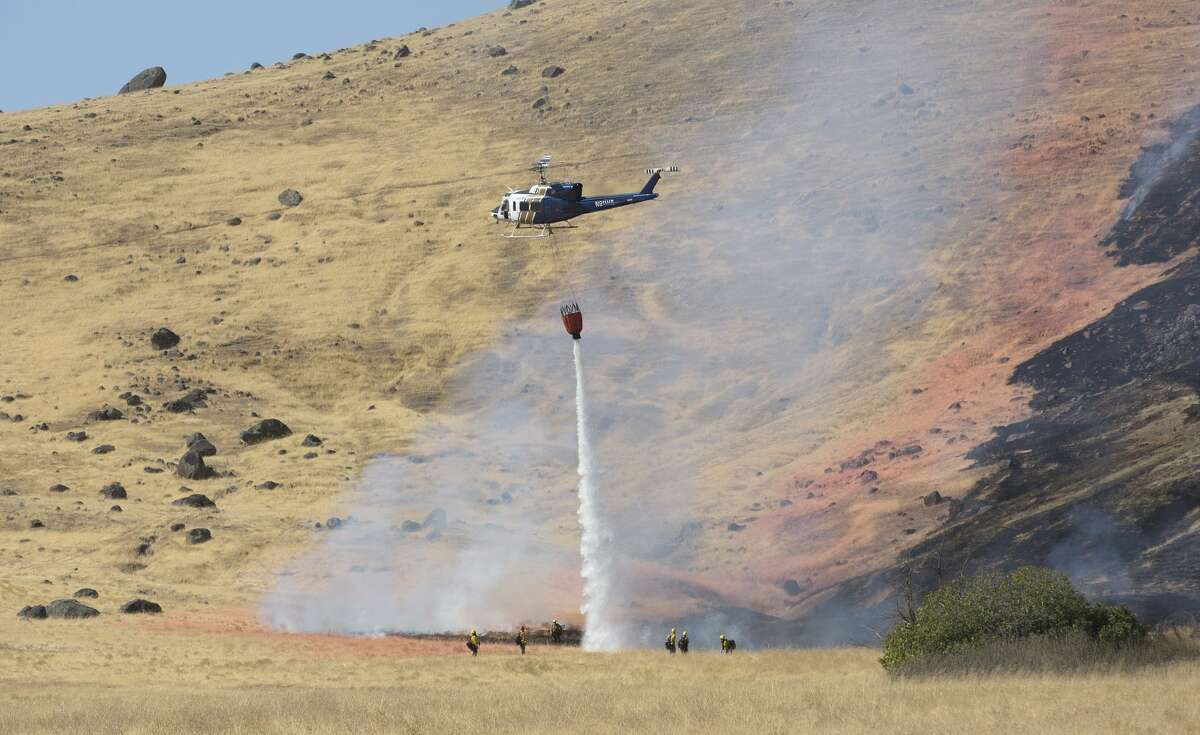 A California Highway Patrol helicopter drops water on a fire caused by the crash of a U.S. Air Force U-2 spy plane in the Sutter Butte Mountains, Tuesday, Sept. 20, 2016, near Yuba City, Calif. The plane had just taken off on a training mission from nearby Beale Air Force Base. The two pilots ejected before the crash. (AP Photo/Rich Pedroncelli)