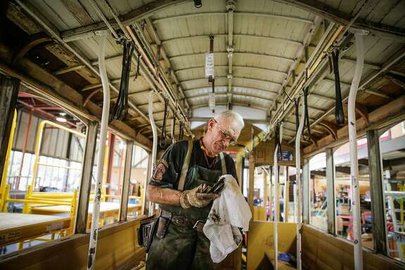 Carpenter John Barberini cleans a piece of metal while repairing cable car #23 at the Cable Car repair shop in the Dogpatch neighborhood, in San Francisco, California, on Tuesday, Sept. 20, 2016.