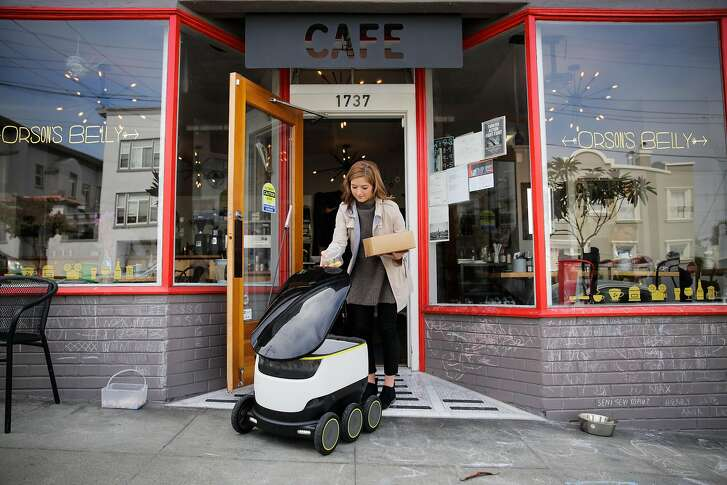 Megan Keesee, who does PR for Starship technologies demonstrates how a Starship delivery robot works as it prepares to do it's first autonomous delivery, in San Francisco, California, on Tuesday, Sept. 20, 2016.