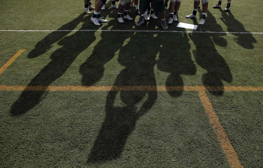 The shadows of Assitant coach Chris Crespi and defensive players working out a defensive play during varsity football practice at De La Salle High School in Concord, Calif., on Tuesday, September 13, 2016. De La Salle plays Antioch High School in a game pitting two bay area football powerhouses, and stopping Najee Harris is the first priority for the Spartans. Photo: Carlos Avila Gonzalez, The Chronicle