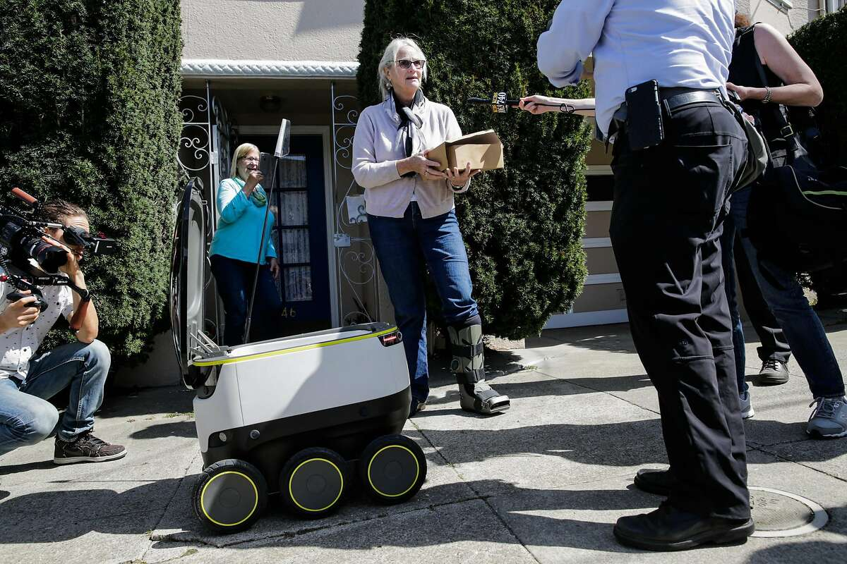 A starship delivery robot makes its first autonomous delivery of pastries to customer Julie O'Keefe (center), in San Francisco, California, on Tuesday, Sept. 20, 2016.