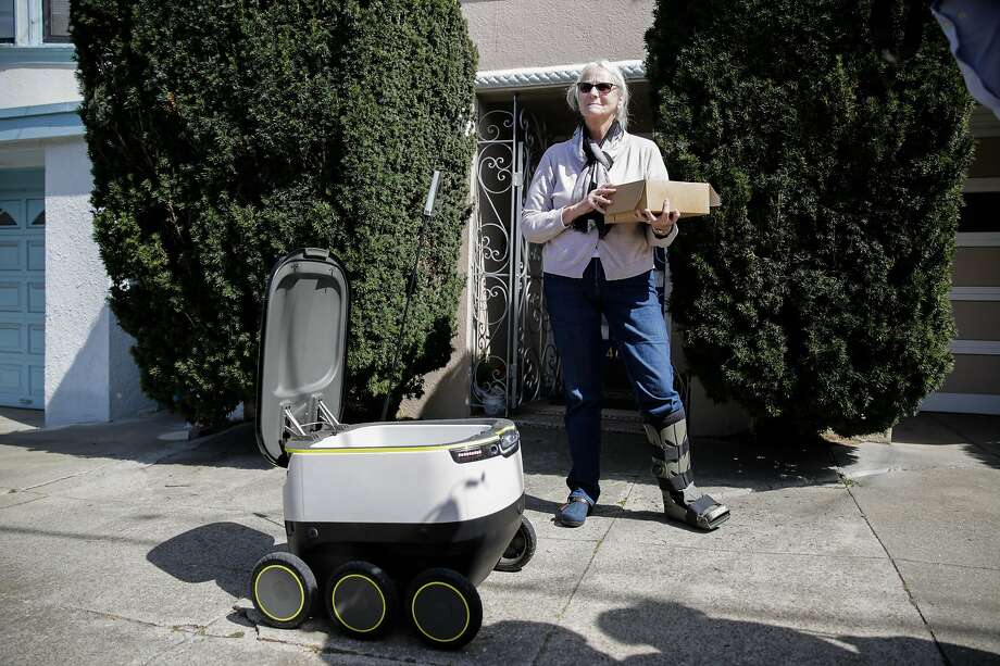 A starship delivery robot makes its first autonomous delivery of pastries  to customer Julie O'Keefe (center), in San Francisco, California, on Tuesday, Sept. 20, 2016. Photo: Gabrielle Lurie, Special To The Chronicle