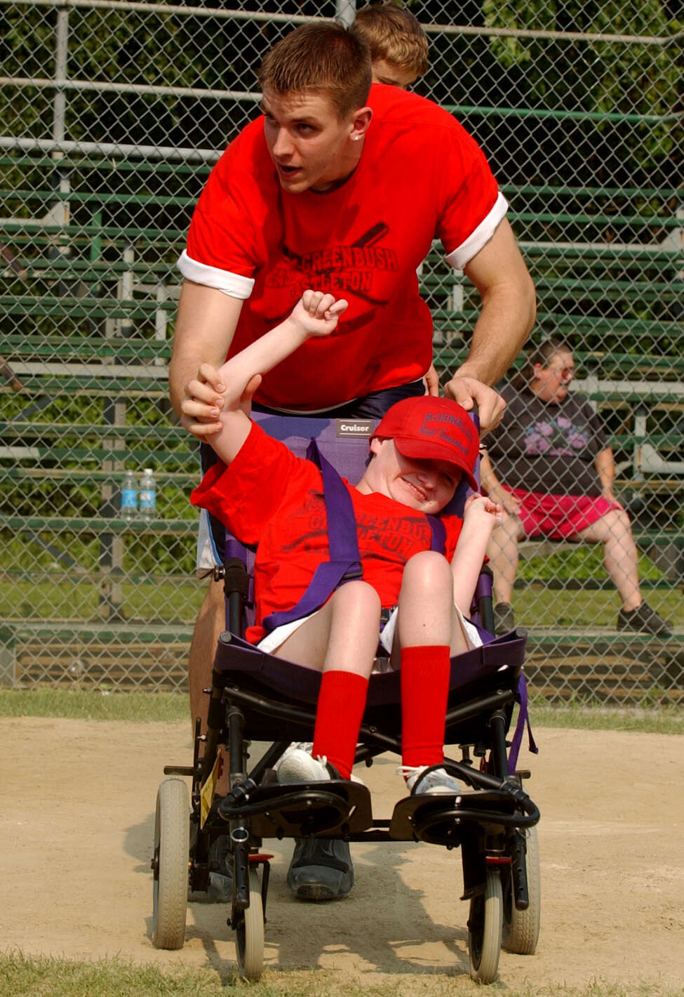 Craig Forth, a former Columbia High basketball star and now a sophomore player at Syracuse University, takes the arm of Jaime Adams as they wave to the crowd after passing home plate at the East Greenbush Little League Field on Monday July 1, 2002, in East Greenbush, N.Y. Forth volunteers his time in a program to help physically challenged children play baseball. (Will Waldron/Times Union)