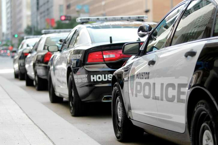 Houston Police Department patrol cars parked outside HPD's downtown headquarters.
