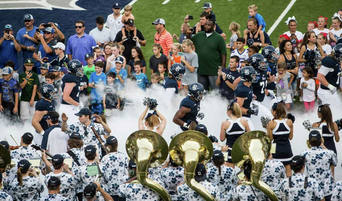 Rice football players run onto the field for an NCAA football game against Baylor as the Marching Owl Band looks on at Rice Stadium on Friday, Sept. 16, 2016, in Houston. ( Brett Coomer / Houston Chronicle )
