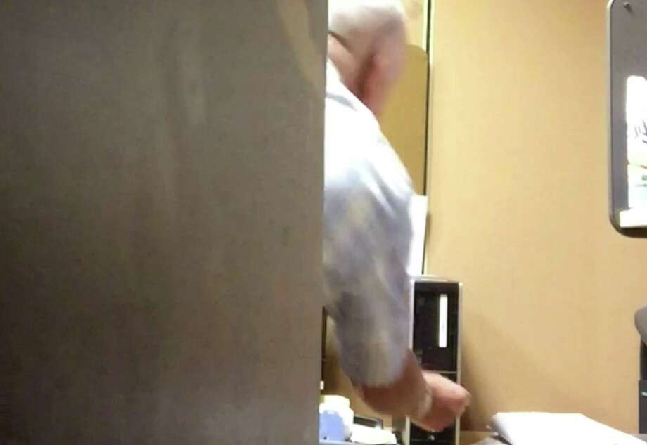 Still frame from surveillance video shot by Mark Karam who is suing the NY Power Authority, contending he was harassed at work. This is a shot of a co-worker allegedly turning off his computer.