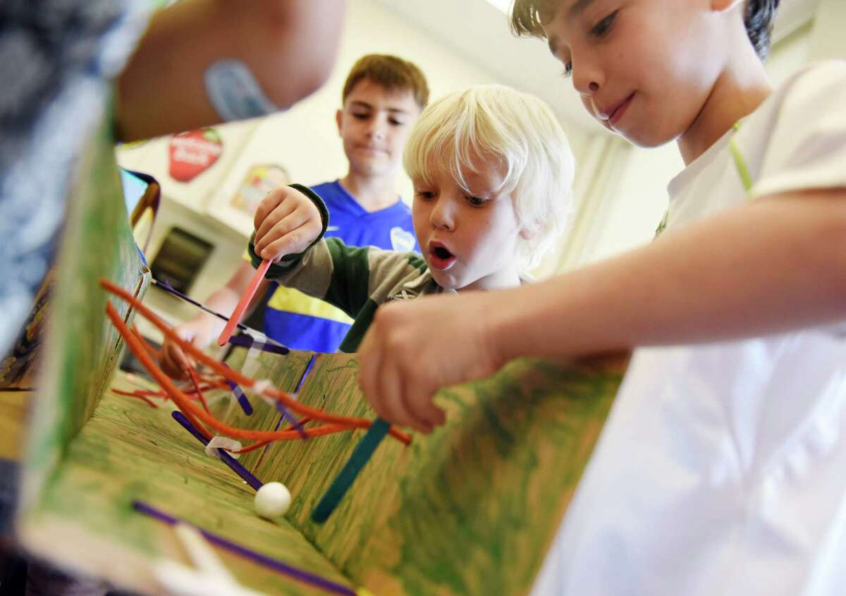 Third-grader Santiago Sirito, left, kindergartener Lucas Pascual, center, and third-grader Tobias Knoll play a popsicle stick soccer game during the Global Cardboard Challenge presentation day at Riverside School in the Riverside section of Greenwich.