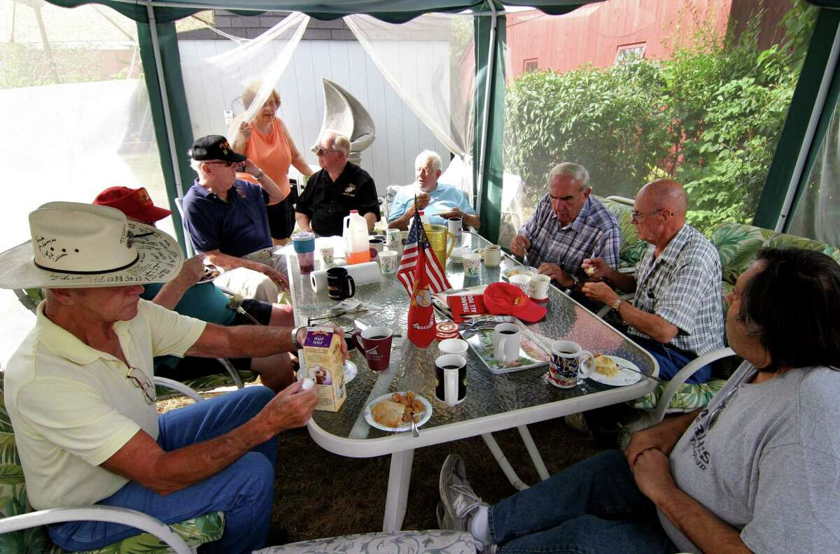 Korean War veteran and US Marine Joseph Cullen, Founder of Marines of Long Ago, seated in back with his wife Phyllis standing left of him, hosts an annual reunion of war veterans, many from the Korean War, at his home in Milford, Conn., on Tuesday Sept. 20, 2016. This annual gathering at Cullen's home features pie and coffee for all who attend. During the event, a special call of support was made to fellow Korean War veteran Sgt. Frank Sturrock, from Texas. The organization, which was started by Cullen about 14 years ago, now boasts over 9,000 marines from past and present.