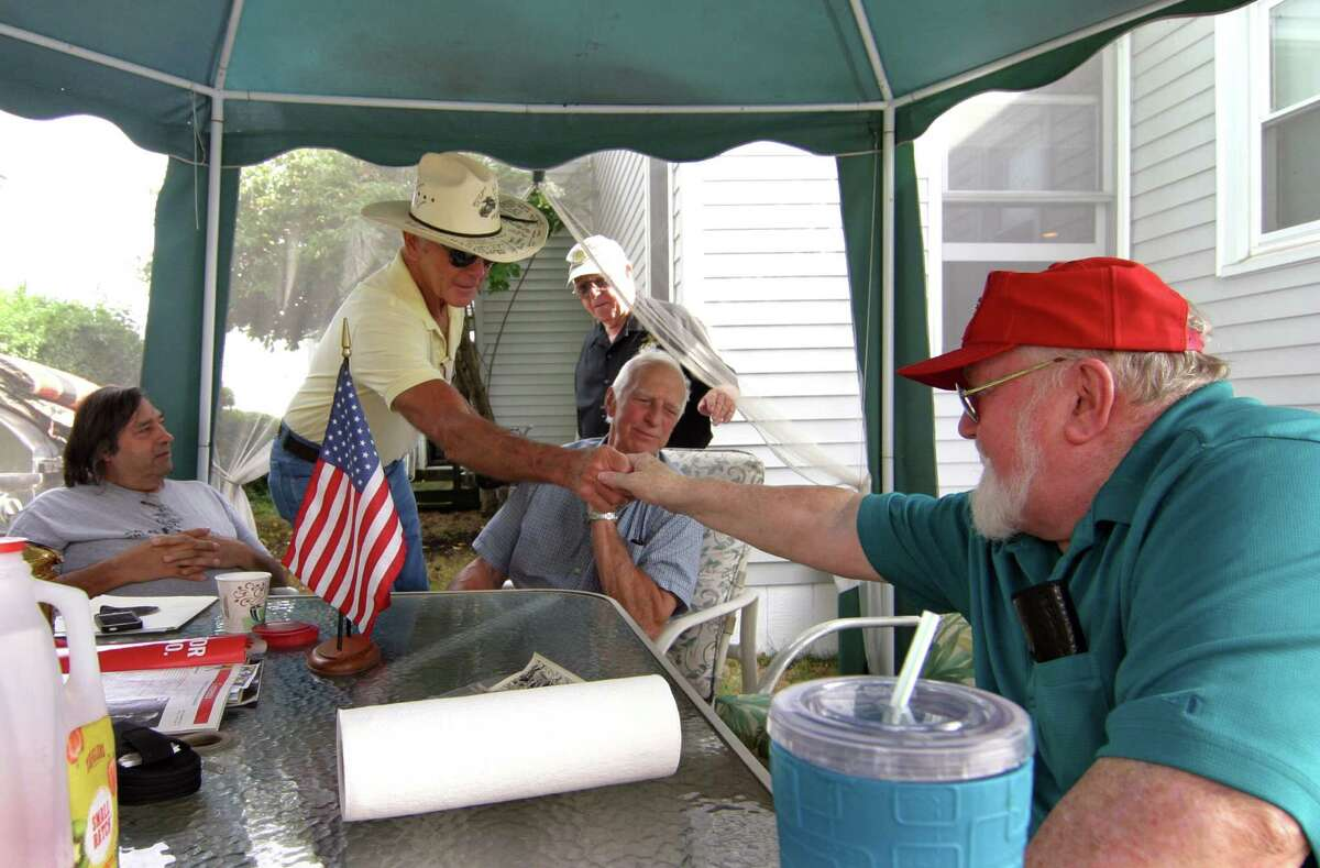 Veterans Bob Cross, of New York, and Don Vogt, of West Haven, greet each other during a reunion of members of the group Marines of Long Ago, at the home of founder Korean War veteran and US Marine Joseph Cullen in Milford, Conn., on Tuesday Sept. 20, 2016. This annual gathering at Cullen's home features pie and coffee for all who attend. During the event, a special call was made to fellow Korean War veteran Sgt. Frank Sturrock, from Texas. The organization, which was started by Cullen about 14 years ago, now boasts over 9,000 marines from past and present.