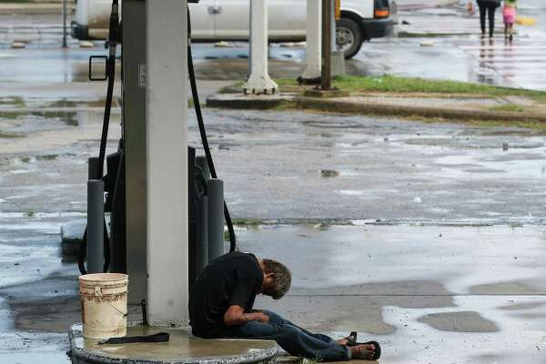 A man sleeps outside a car repair shop Tuesday at the corner of North Main and Quitman, a common occurrence in the Near Northside neighbor-hood, residents say.