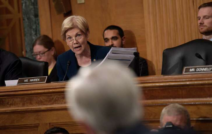 Senate Banking Committee member Sen. Elizabeth Warren, D-Mass., left, holds up transcripts of earnings calls as she questions Wells Fargo Chief Executive Officer John Stumpf, on Capitol Hill in Washington, Tuesday, Sept. 20, 2016, during the committee's hearing. Stumpf was called before the committee for betraying customers' trust in a scandal over allegations that employees opened millions of unauthorized accounts to meet aggressive sales targets. (AP Photo/Susan Walsh)