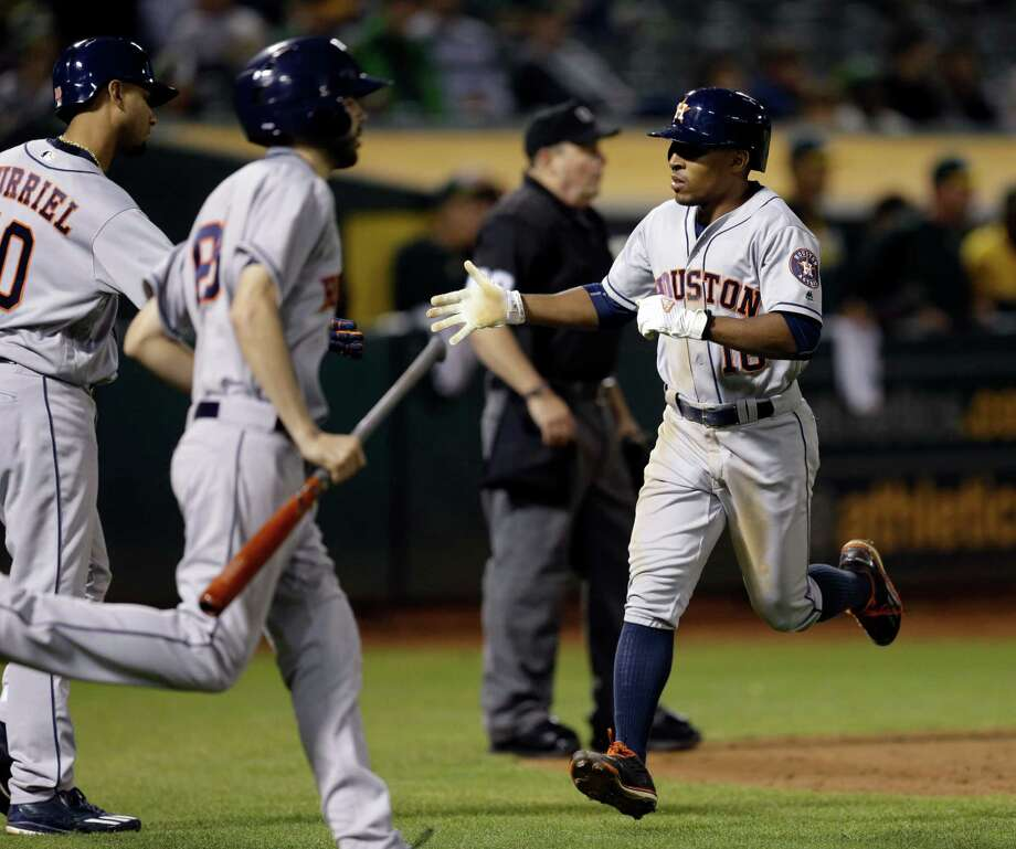 Houston Astros' Tony Kemp, right, celebrates with Yulieski Gurriel, left, after scoring against the Oakland Athletics in the tenth inning of a baseball game Tuesday, Sept. 20, 2016, in Oakland, Calif. (AP Photo/Ben Margot) Photo: Ben Margot, Associated Press / Copyright 2016 The Associated Press. All rights reserved.
