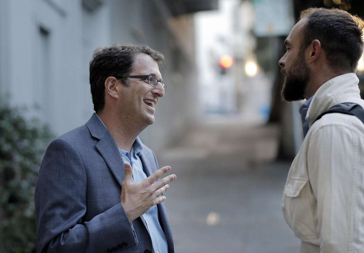 Dean Preston, candidate for the district 5 supervisor, left, chats with Bryan Gates outside his home as Preston canvases the district on Golden Gate Avenue in San Francisco, Calif., on Tuesday, September 20, 2016.