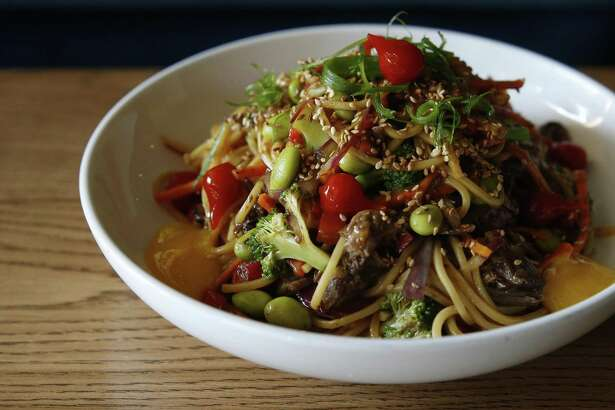 The asado criollo noodles with braised beef short ribs, edamame, egg noodles, sprouted mung beans, sofrito, aji amarillo and soft yolk.