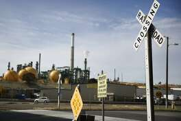 The Valero refinery is seen in the background behind signage for a railroad crossing on Wednesday, October 22, 2014 in Benicia, Calif.