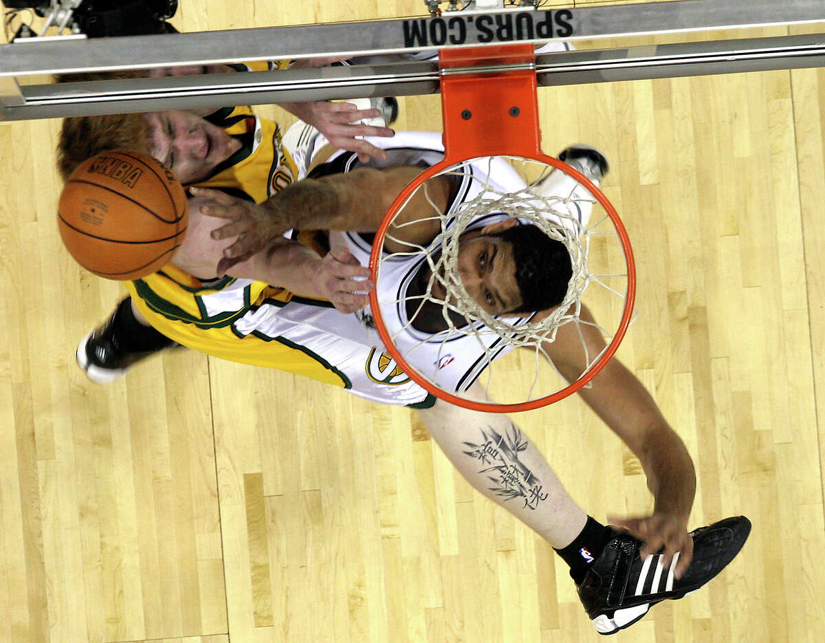 Tim Duncan blocks Seattle Supersonics center Robert Swift during the first quarter of play at the AT&T Center in San Antonio, TX Tuesday, April 11, 2006. (MIKE KANE)